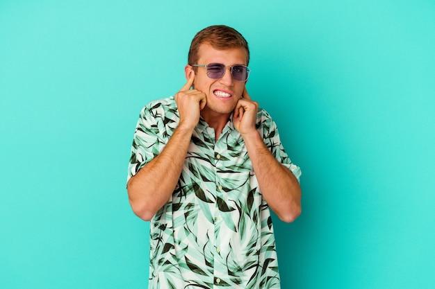 손으로 귀를 덮고 파란색에 고립 된 여름 옷을 입고 젊은 백인 남자.