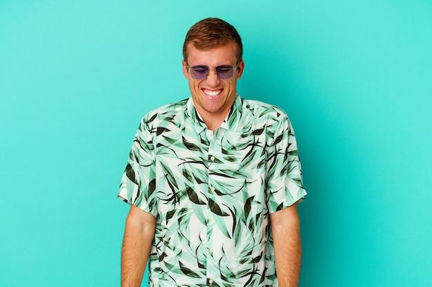 青いで隔離された夏服を着ている若い白人男性は、笑って目を閉じ、リラックスして幸せを感じます。