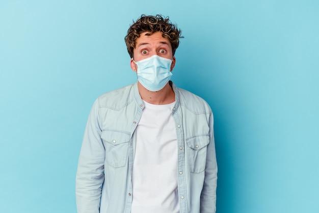 Молодой кавказский человек, носящий противовирусную маску, изолированную на синем фоне, пожимает плечами и смущенно открывает глаза.