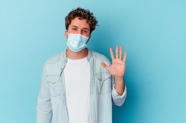 青い背景に分離された抗ウイルスマスクを身に着けている若い白人男性は、指で5番を示して陽気に笑っています。