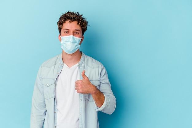 Молодой кавказский мужчина в противовирусной маске, изолированный на синем, улыбается и поднимает большой палец вверх