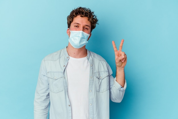 Молодой кавказский мужчина в противовирусной маске на синей стене радостный и беззаботный показывает пальцами символ мира