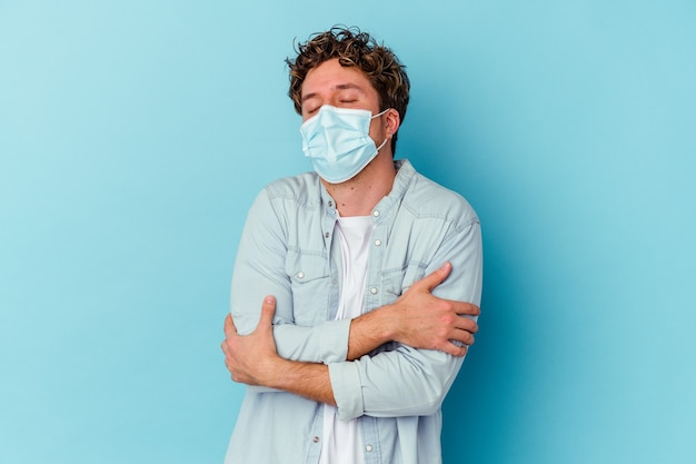 Young caucasian man wearing an antiviral mask isolated on blue background hugs, smiling carefree and happy.