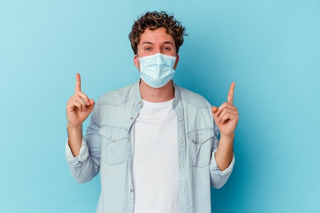 Young caucasian man wearing an antiviral mask isolated on blue wall indicates with both fore fingers up showing a blank space.