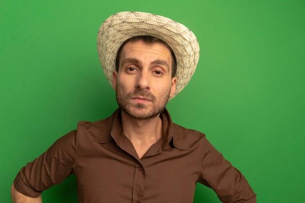 Cappello da portare della spiaggia del giovane uomo caucasico che tiene le mani sulla vita isolata sulla parete verde