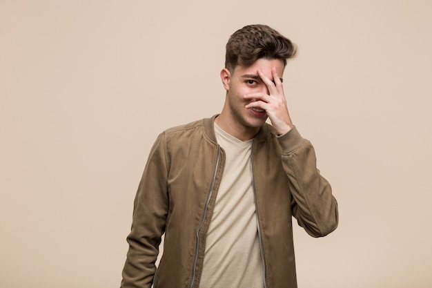 Young caucasian man wearing a brown jacket blink at the camera through fingers, embarrassed covering face.
