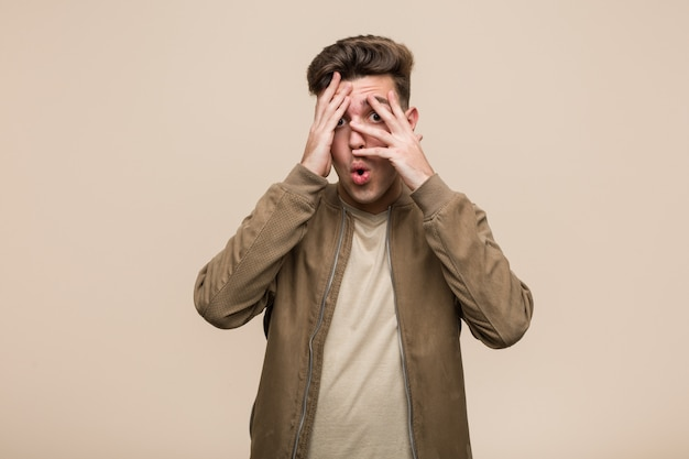 Young caucasian man wearing a brown jacket blink through fingers frightened and nervous.