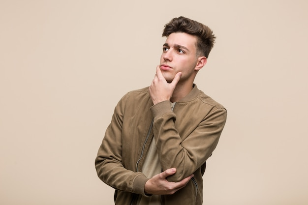 Young caucasian man wearing a brown jacket looking sideways with doubtful and skeptical expression.
