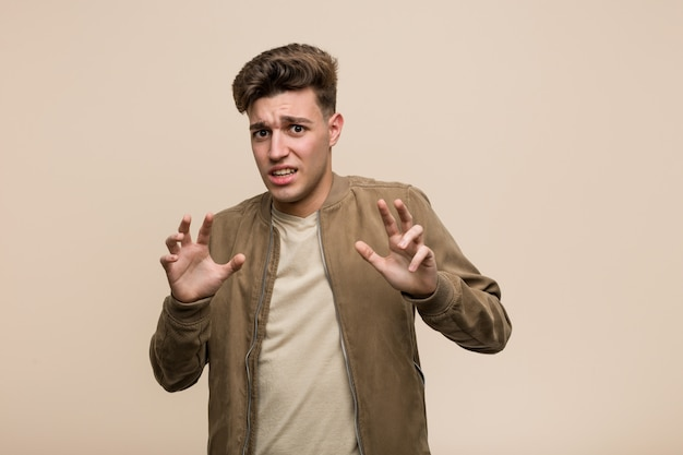 Young caucasian man wearing a brown jacket rejecting someone showing a gesture of disgust.