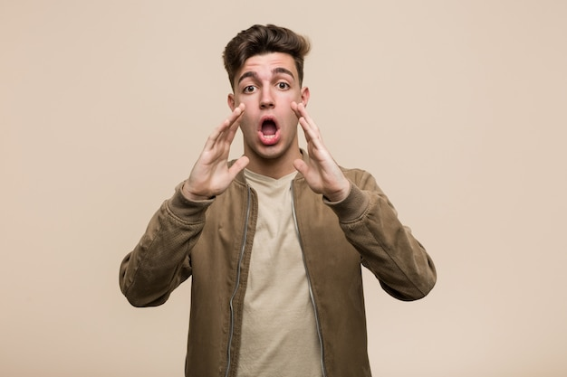 Young caucasian man wearing a brown jacket shouting excited to front.