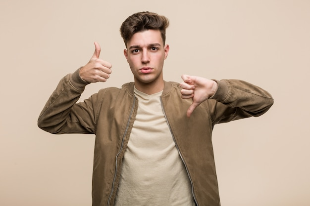 Young caucasian man wearing a brown jacket showing thumbs up and thumbs down, difficult choose