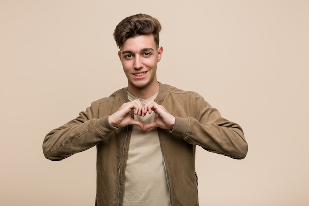 Young caucasian man wearing a brown jacket smiling and showing a heart shape with him hands.