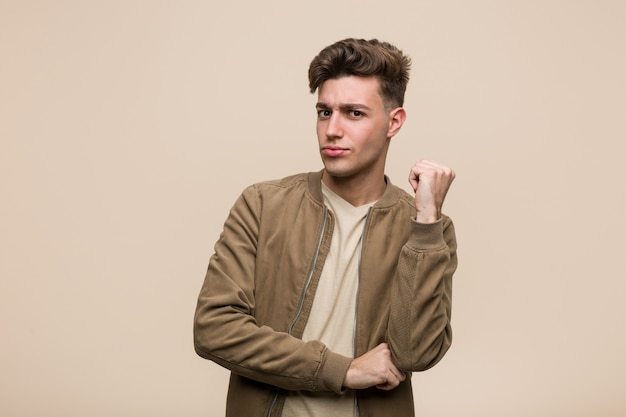 Young caucasian man wearing a brown jacket thinking and making a choice.