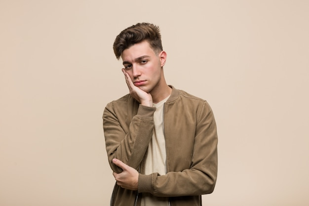 Young caucasian man wearing a brown jacket who is bored, fatigued and need a relax day.