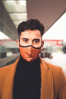 Young caucasian man wearing a brown mask with a brown coat at the street