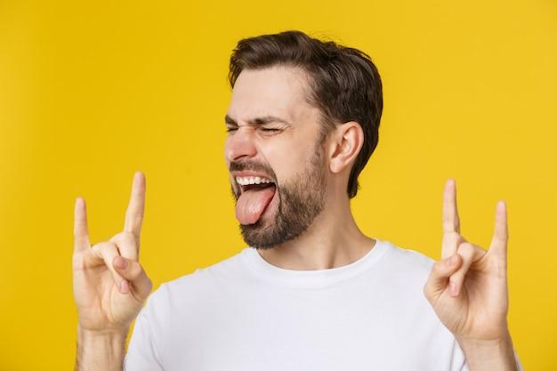 Молодой кавказский человек нося вскользь футболку над желтым цветом изолировал кричать с шальным выражением делая символ утеса с руками вверх