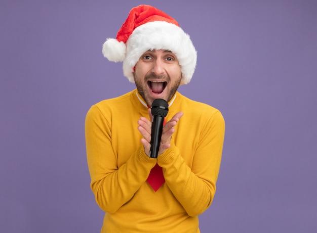 コピースペースと紫色の背景に分離されたカメラの歌を見て、クリスマスの帽子とネクタイ保持マイクを身に着けている若い白人男性