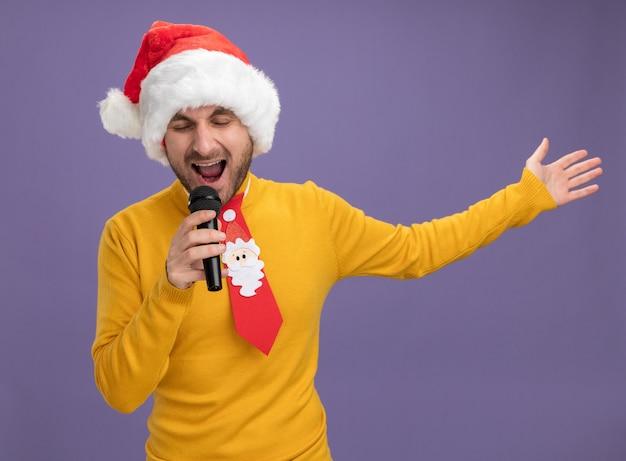 クリスマスの帽子とネクタイを身に着けている若い白人男性が紫色の背景で隔離の手を伸ばして目を閉じて歌うマイクを保持します。