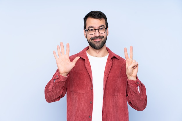 Young caucasian man wearing corduroy jacket over blue wall counting seven with fingers