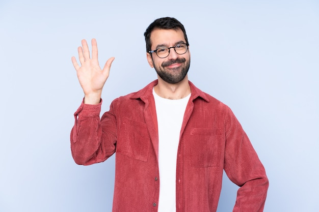 Young caucasian man wearing corduroy jacket over blue wall saluting with hand with happy expression