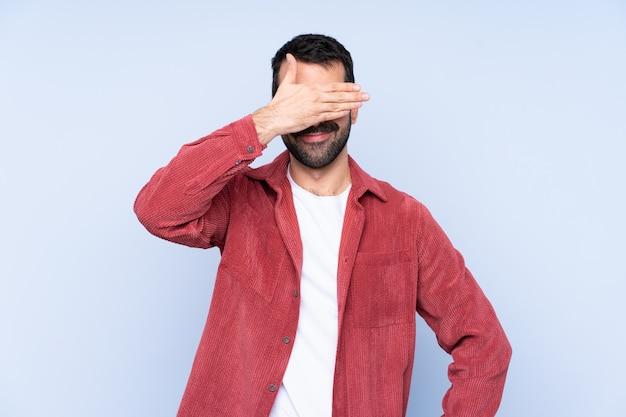 Куртка вельвета молодого кавказского человека нося над голубыми глазами заволакивания стены руками. не хочу что-то видеть Premium Фотографии