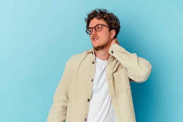 Young caucasian man wearing eyeglasses isolated on blue background having a neck pain due to stress, massaging and touching it with hand.