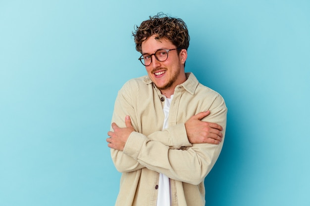 Young caucasian man wearing eyeglasses isolated on blue background hugs, smiling carefree and happy.