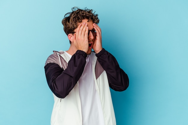 Young caucasian man wearing eyeglasses isolated on blue wall afraid covering eyes with hands.