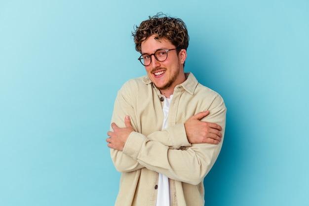파란색 배경에 고립 된 안경을 쓰고 젊은 백인 남자는 평온하고 행복 미소, 포옹.