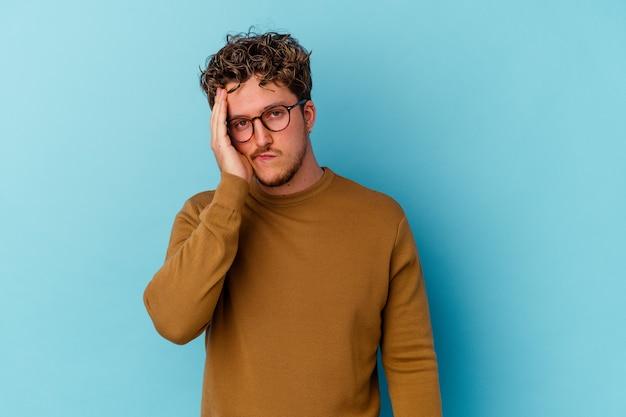 파란색 배경에 고립 된 안경을 쓰고 젊은 백인 남자 피곤 하 고 매우 졸려 머리에 손을 유지.