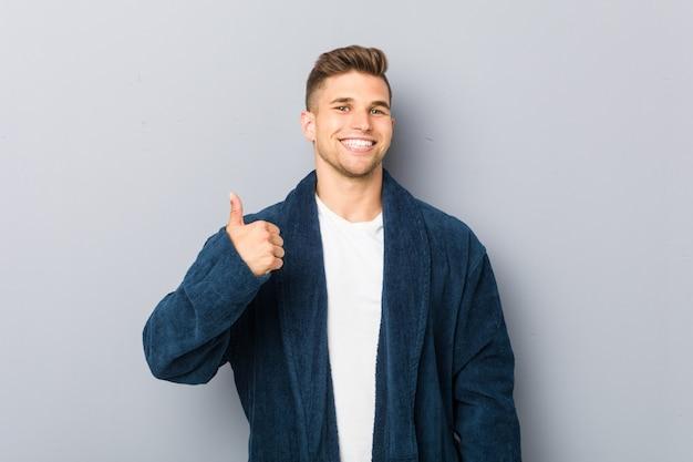 Young caucasian man wearing pajama smiling and raising thumb up
