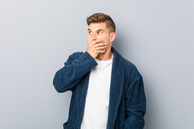 Young caucasian man wearing pajama thoughtful looking to a copy space covering mouth with hand.