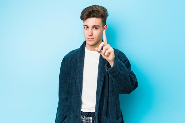 指でナンバーワンを示すパジャマを着ている若い白人男。