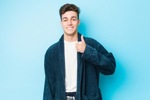 Young caucasian man wearing pajamas smiling and raising thumb up
