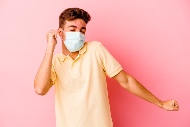 Young caucasian man wearing a protection for coronavirus isolated on pink wall dancing and having fun.
