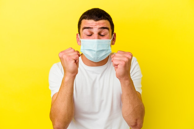 Young caucasian man wearing a protection for coronavirus isolated on yellow wall raising fist, feeling happy and successful