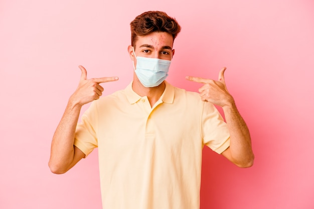 Young caucasian man wearing a protection for coronavirus on pink smiles, pointing fingers at mouth.