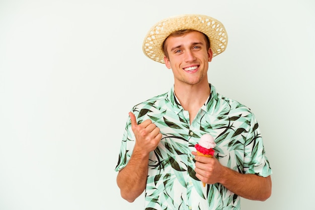 Young caucasian man wearing a summer clothes and holding a ice cream isolated on white smiling and raising thumb up
