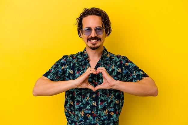 웃 고 손으로 심장 모양을 보여주는 노란색 배경에 고립 된 여름 옷을 입고 젊은 백인 남자.