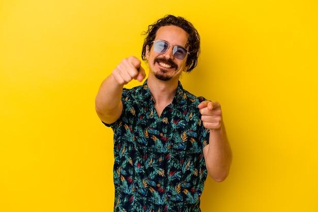 앞을 가리키는 노란색 밝은 미소에 고립 된 여름 옷을 입고 젊은 백인 남자.