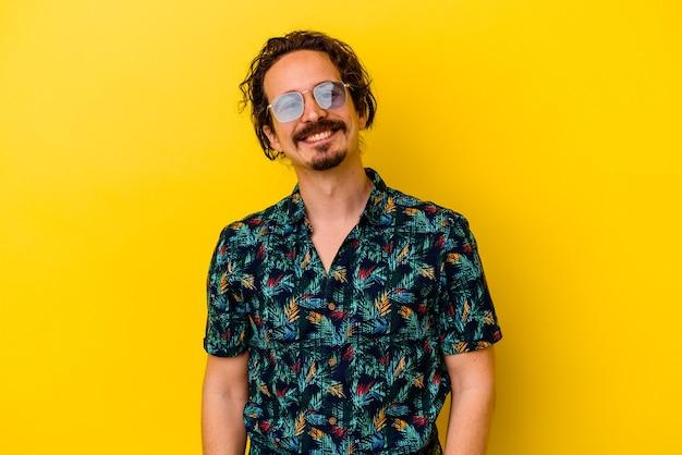 행복 하 고 웃 고 쾌활 한 노란색에 고립 된 여름 옷을 입고 젊은 백인 남자.