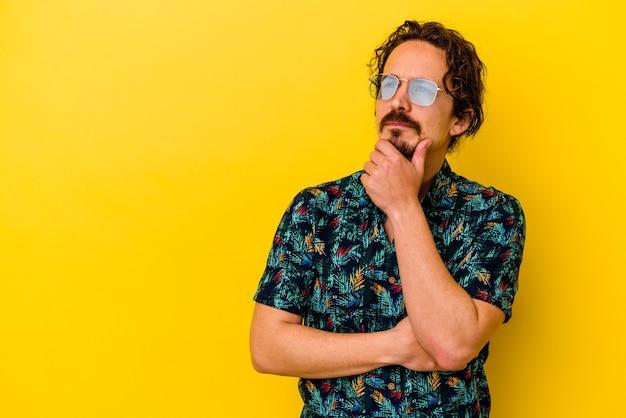 의심스럽고 회의적인 표정으로 옆으로 찾고 노란색에 고립 된 여름 옷을 입고 젊은 백인 남자.