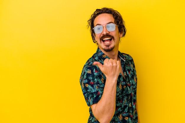 엄지 손가락으로 멀리, 웃음과 평온한 노란색 점에 고립 된 여름 옷을 입고 젊은 백인 남자.