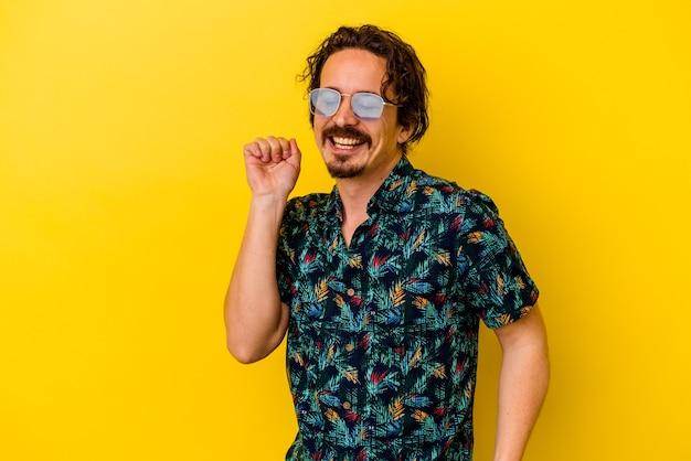 노란색 벽 춤과 재미에 고립 된 여름 옷을 입고 젊은 백인 남자.