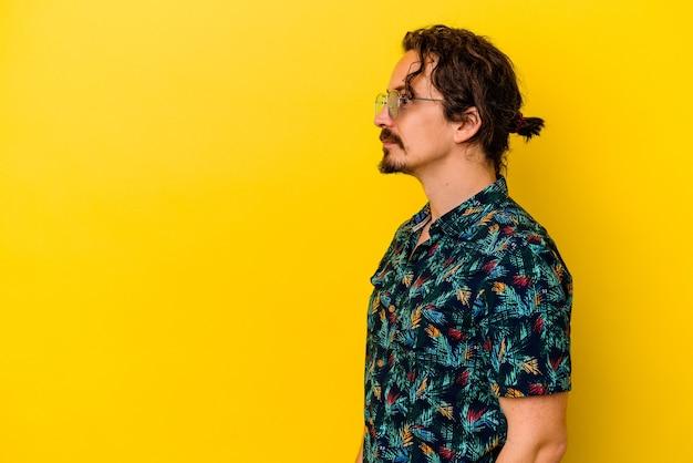 왼쪽, 옆으로 포즈를 응시하는 노란색 벽에 고립 된 여름 옷을 입고 젊은 백인 남자.
