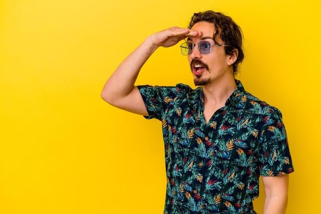 이마에 손을 유지 멀리 멀리 찾고 노란색 벽에 고립 된 여름 옷을 입고 젊은 백인 남자.