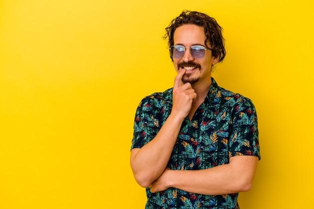 노란색 벽에 고립 된 여름 옷을 입고 젊은 백인 남자 복사본 공간을보고 뭔가에 대해 생각을 편안 하 게합니다.