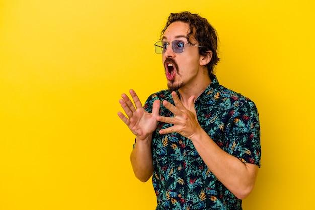 노란색 벽에 고립 된 여름 옷을 입고 젊은 백인 남자는 큰 소리로 외치고, 눈을 뜨고 손을 긴장합니다.