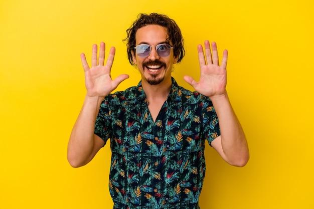 黄色の壁に隔離された夏服を着ている若い白人男性は、手で10番を示しています。
