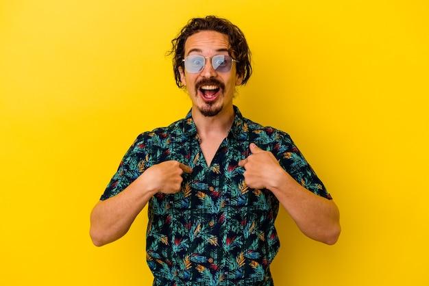 노란색 벽에 고립 된 여름 옷을 입고 젊은 있으면 백인 남자 광범위 하 게 웃 고 손가락으로 가리키는 놀 랐 다.